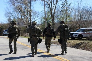 Rutherford County Sheriff's SWAT Team members walk toward a barricaded suspect's home Wednesday on Bradyville Pike.